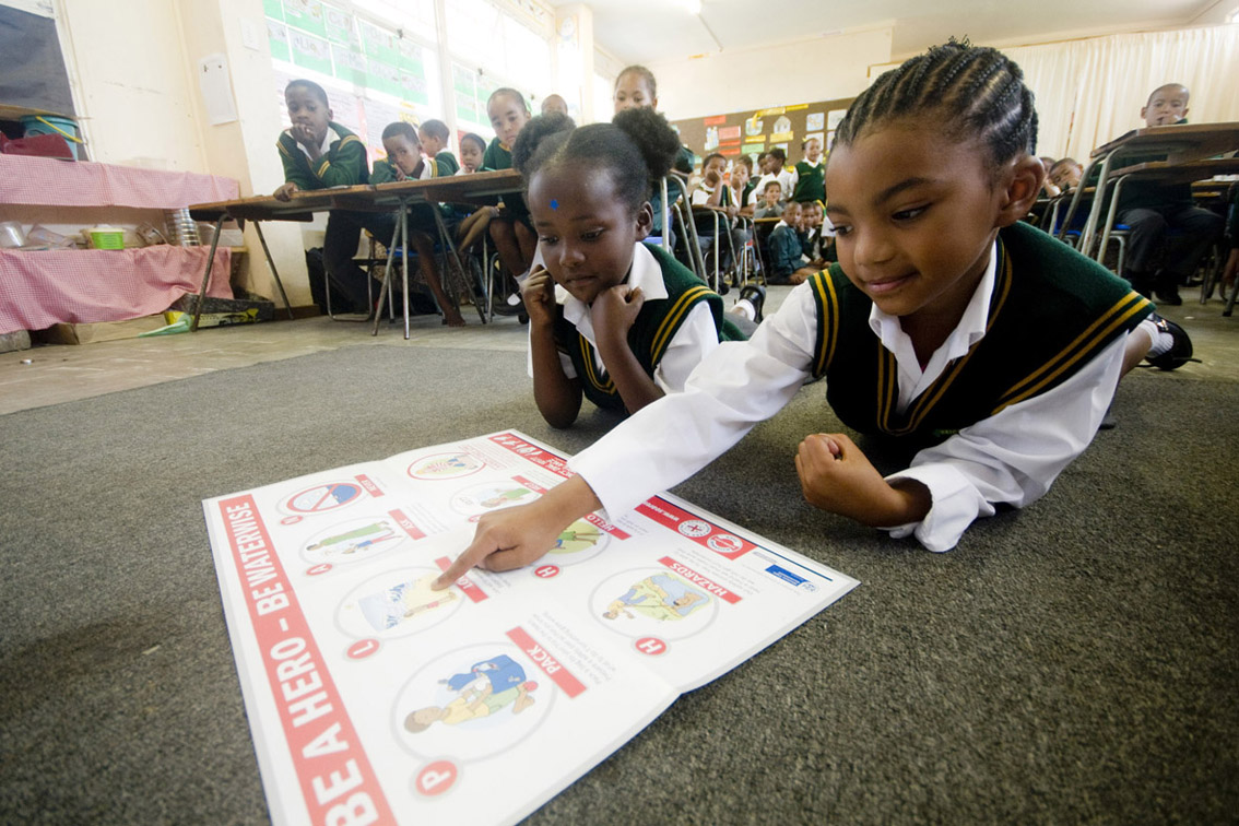 Beronique 7, Libongo 6 from Heidedal Primary looking at the poster that is given to their class.