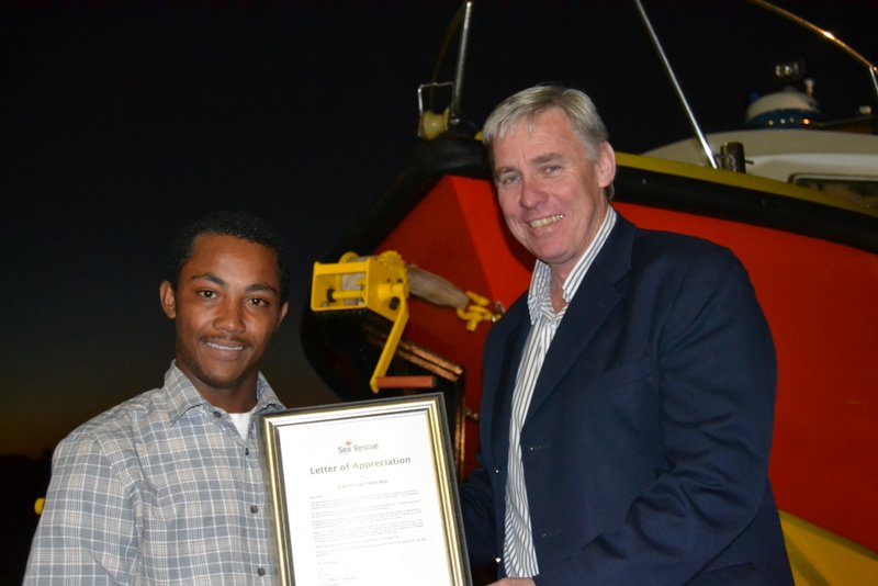 Calvin Hendricks received a Letter of Appreciation for his role in saving 2 men from drowning. Dr. Cleve Robertson is doing the handover. Photo: Mark Duckitt