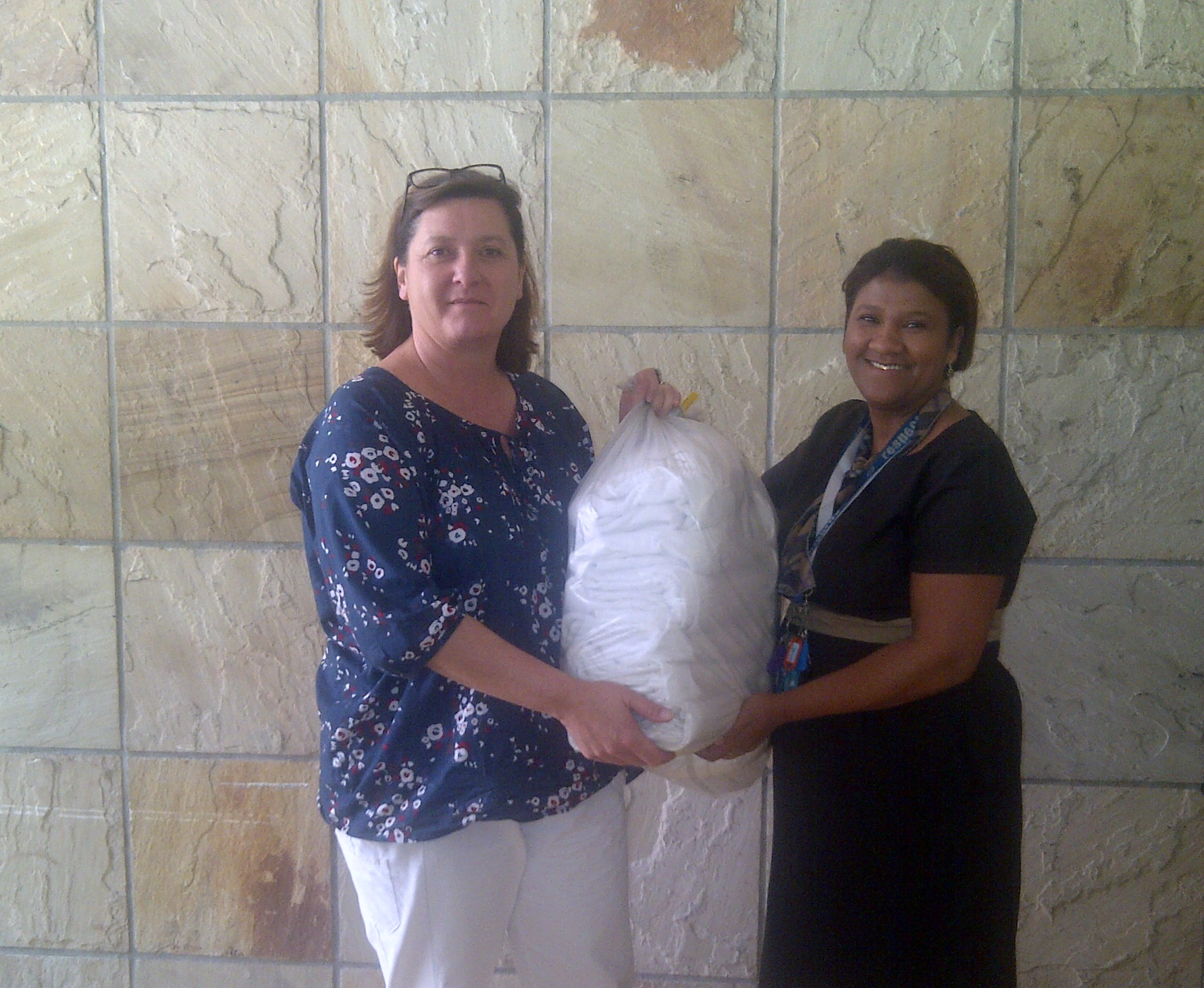 Head of Donor Support, Alison Smith, receives one of the bundles of towels from Natasha Engel, Linen Keeper at the hotel.