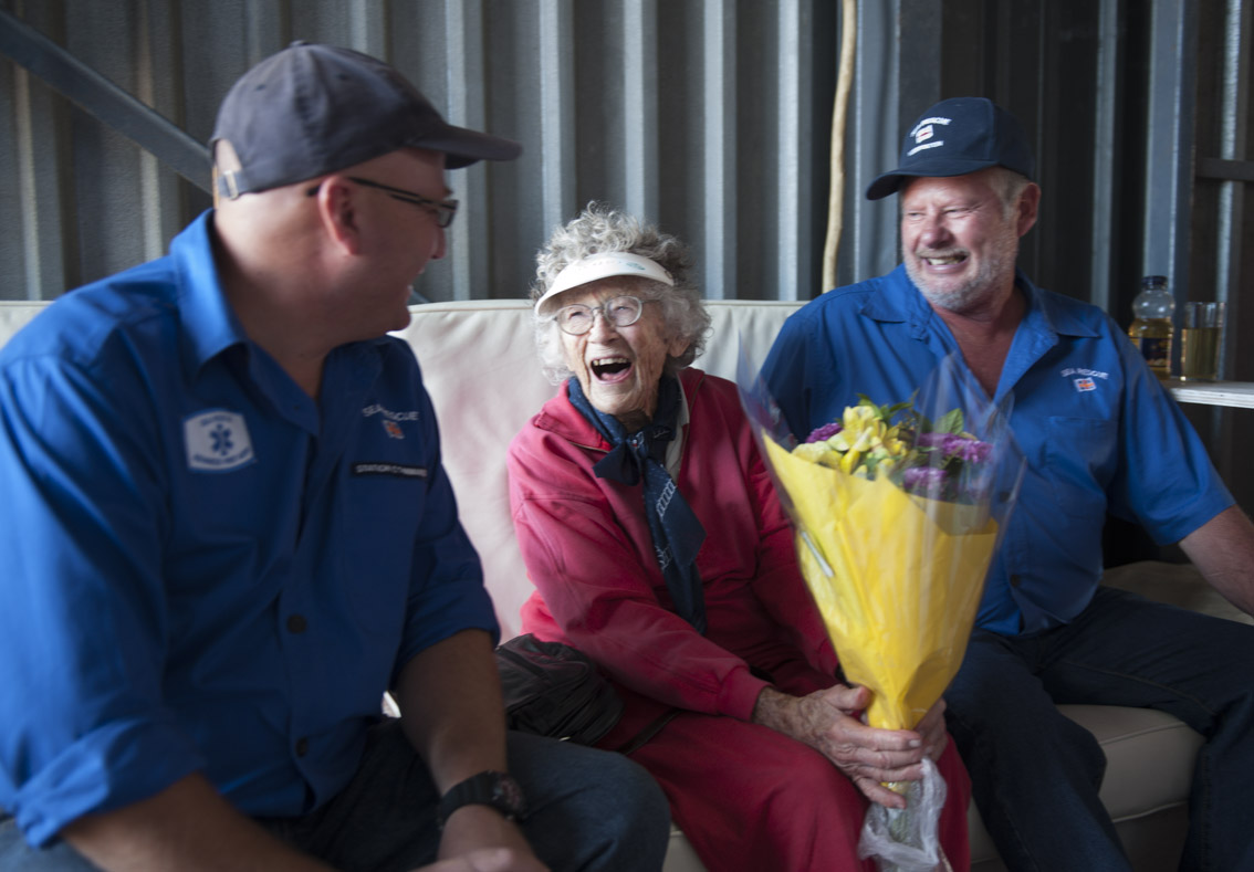 Yzerfontein NSRI volunteers Rudi Rogers and Pieter Rossouw give Georgina flowers.100 year old Georgina Haywood did a parashute jump in aid of Sea Rescue - to raise funds for buying lifejackets for the NSRI volunteers.