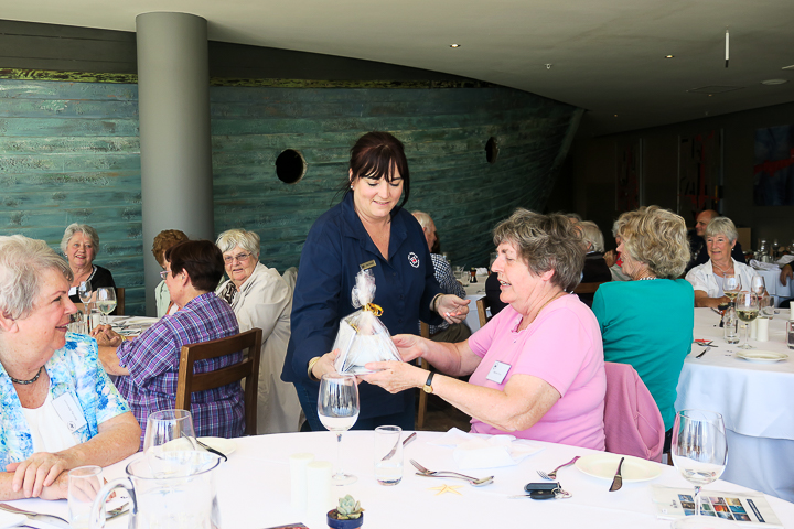 One of the raffle winners being presented with a gift by Kim Gresse