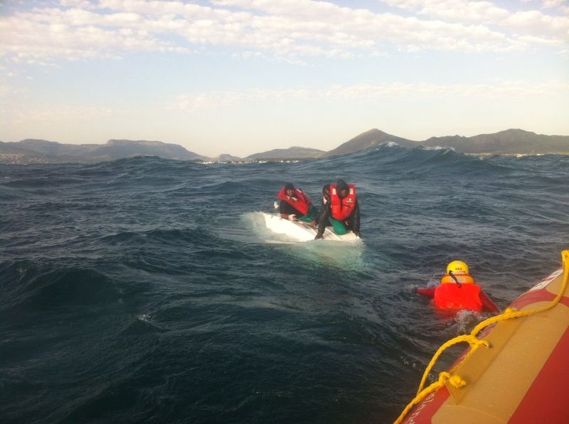 The last two fisherman on their upturned hull before being rescued. Picture Tom Coetzee/NSRI