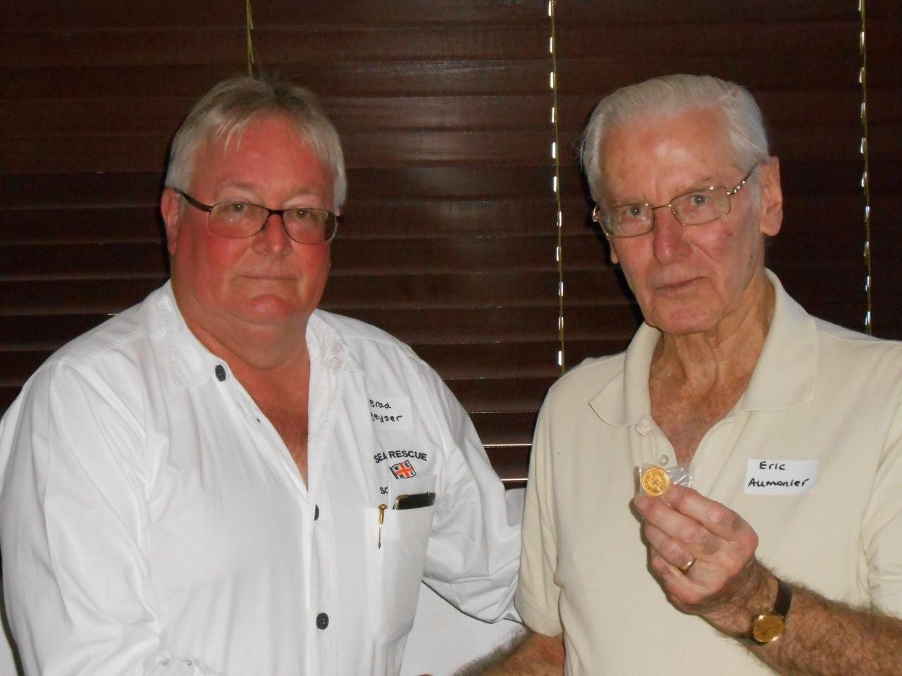 Brad Geyser hands over a gold bequestor's badge to proud supporter Eric Aumonier.