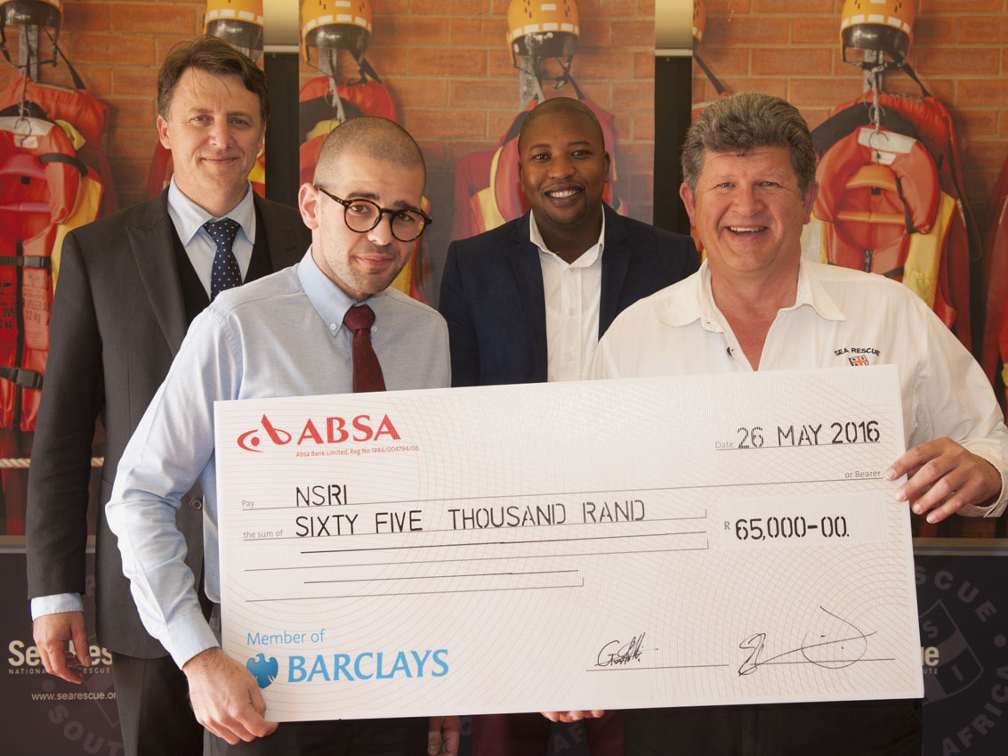 David Jordaan, Gerrit Schmidt III and Leeroy Ndlovu hand over a symbolic cheque to Andre Fraser, NSRI Mossel Bay station commander.