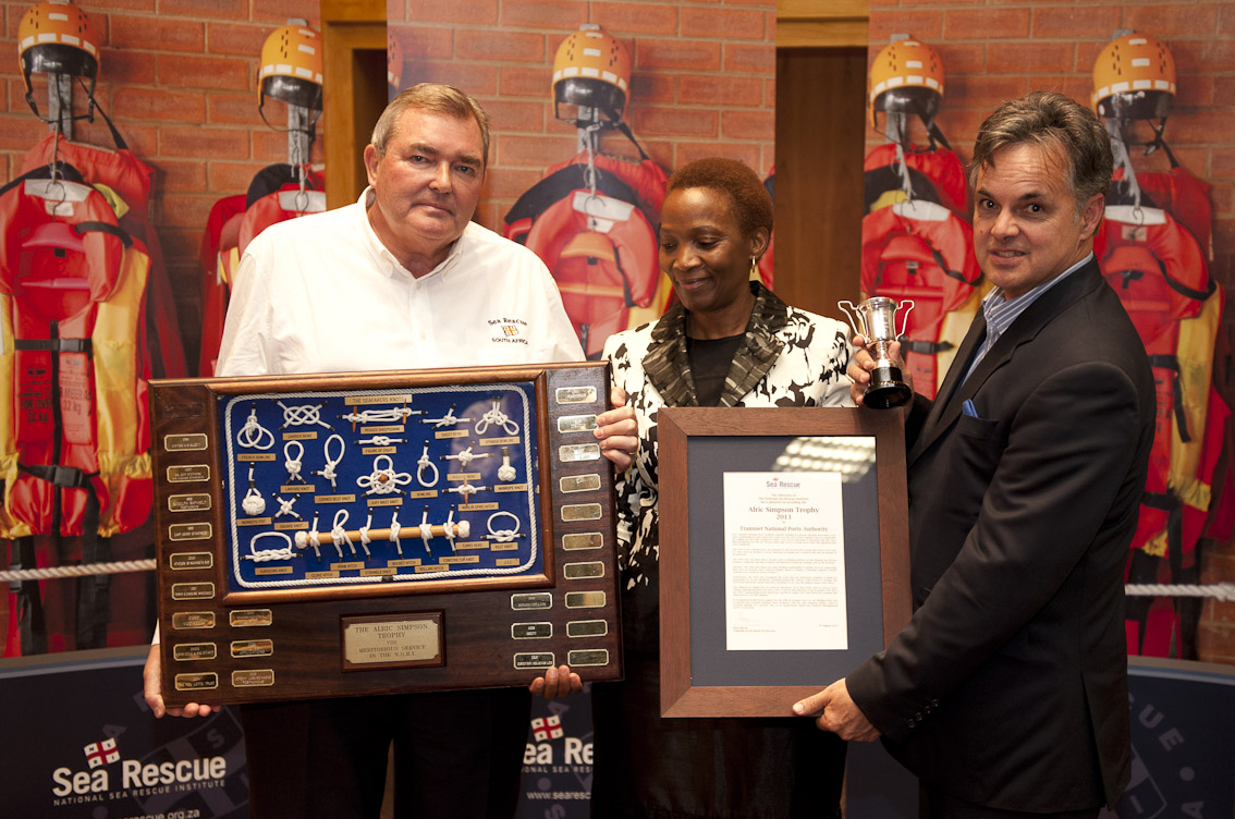 Peter Bacon presents Thandi Mlangeni and Coen Birkenstock of TNPA with the Alric Simpson trophy.