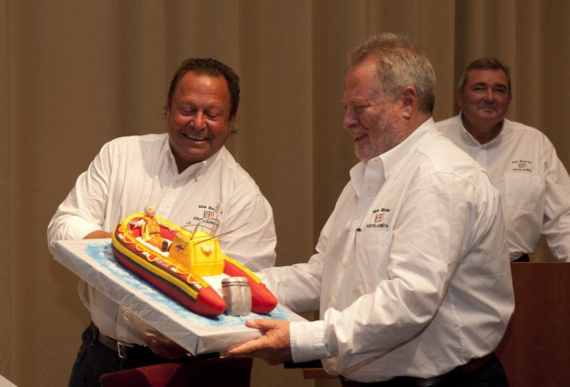 Howard Godfrey presents Ian Wienburg with a Sea Rescue boat cake.