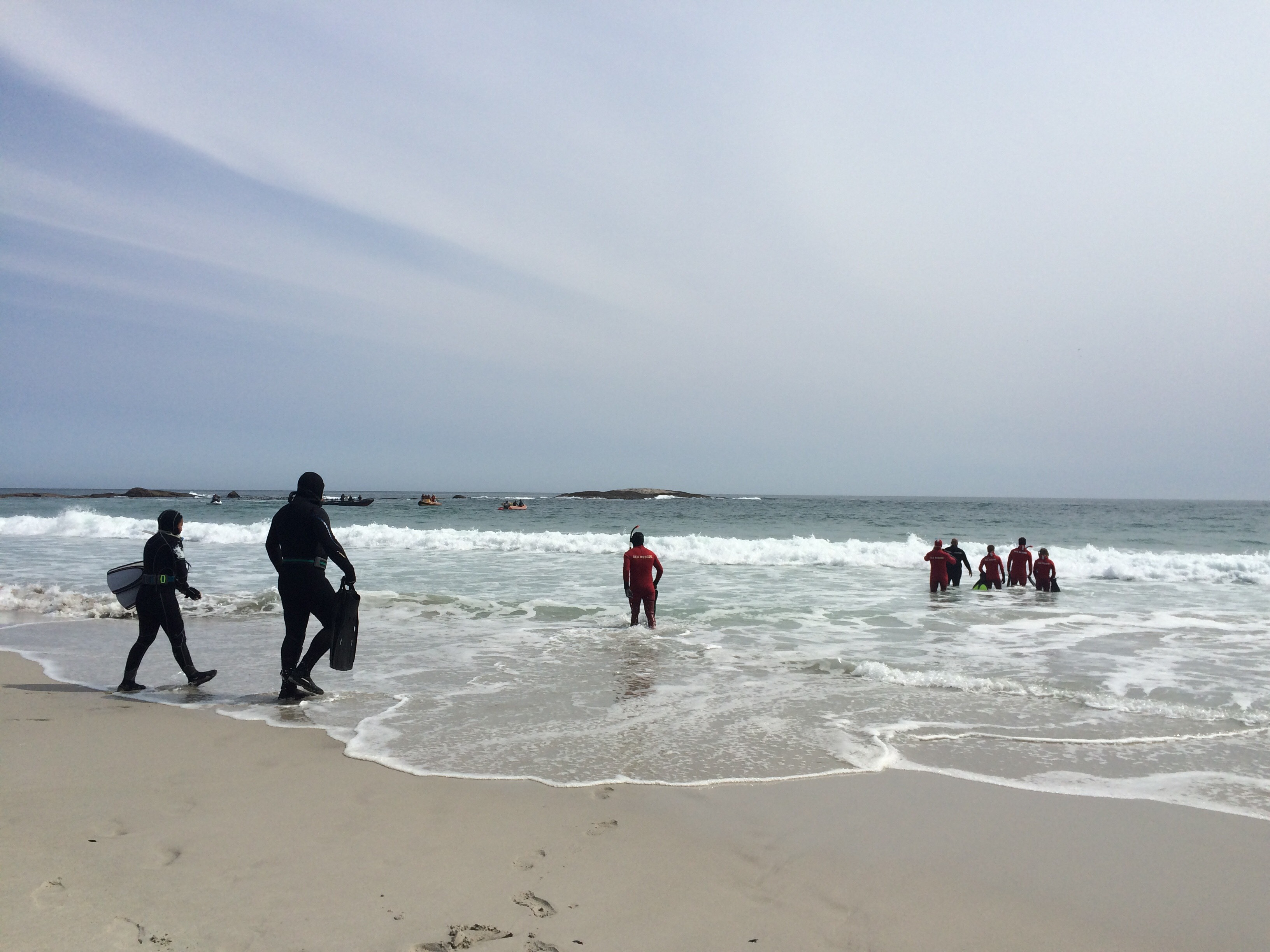 Swimmers and divers enter the water to search.