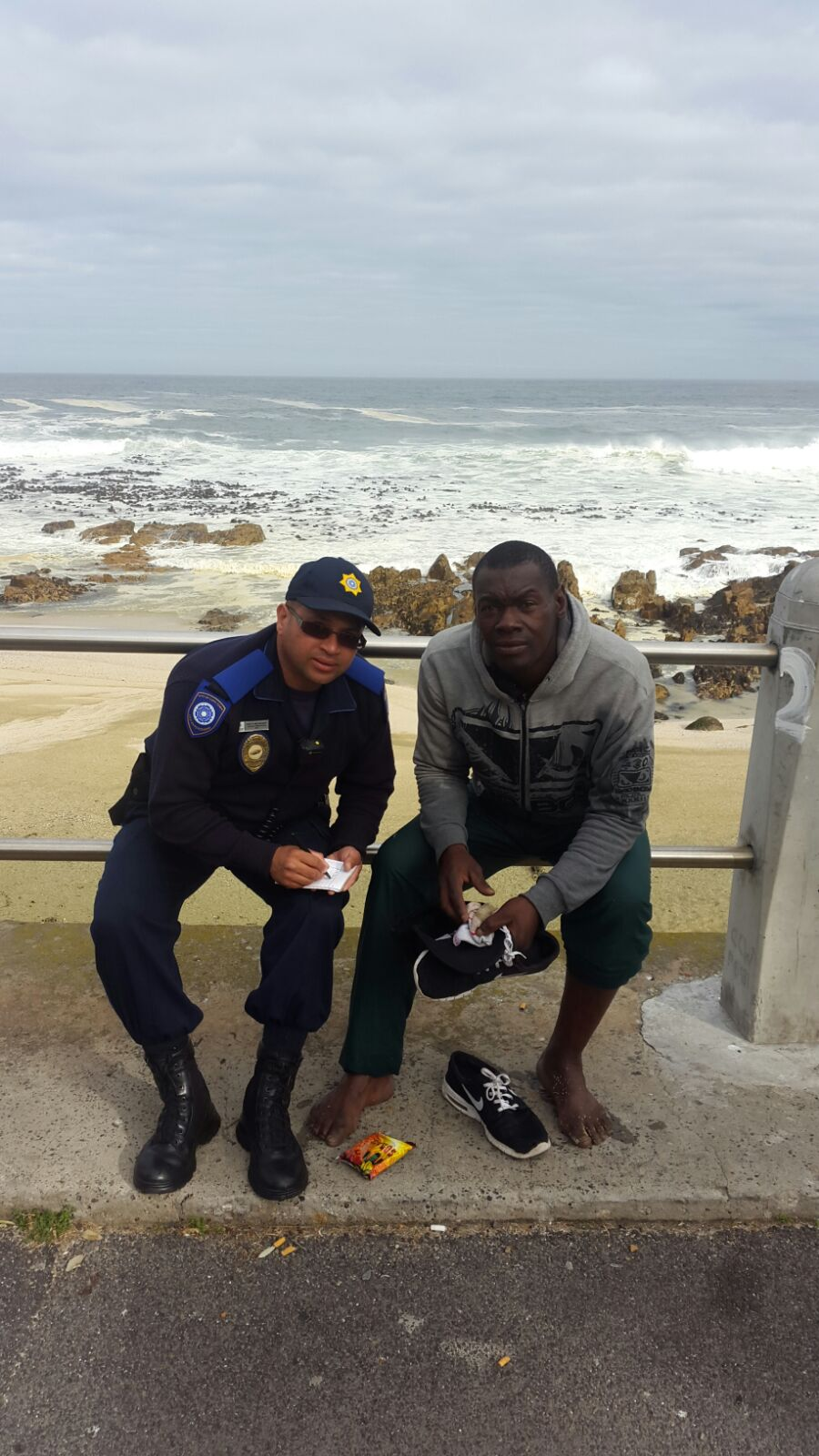 Thembinkosi Gqotso, who rescued a 38 year old Limpopo man from the sea at Queens Beach, Sea Point, gives details of the incident to Law Enforcement officer Maxwell van Wyk Picture by Shane Fascio, ER24