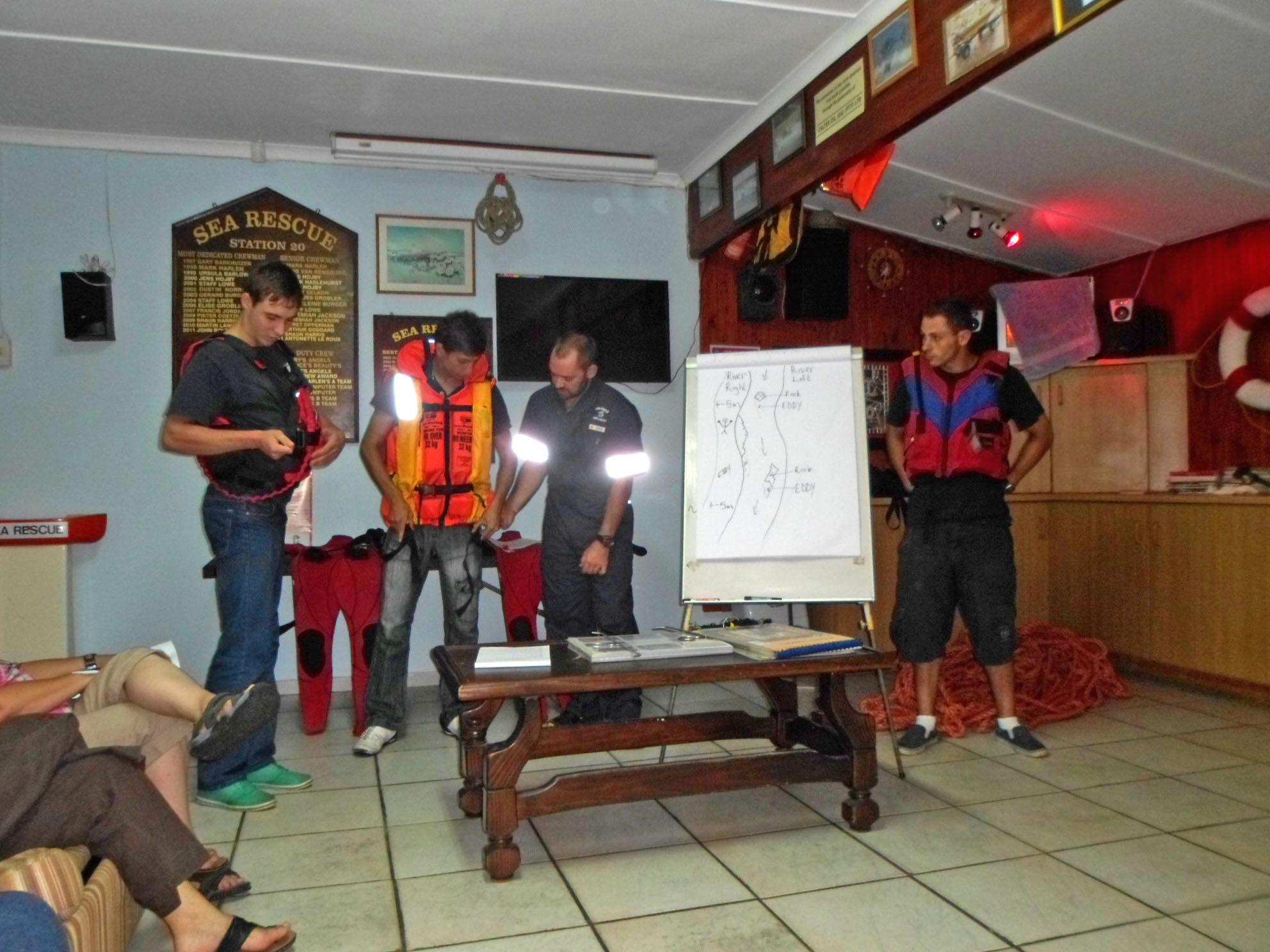 Duty Coxswain, Jerry Jackson, explains to trainees the difference between Personal Flotation Devices (PFDs) used in rivers and lifejackets used at sea. From left, Morne Beattie, Adriaan Devenage, Jerry Jackson and Jason Frewin.