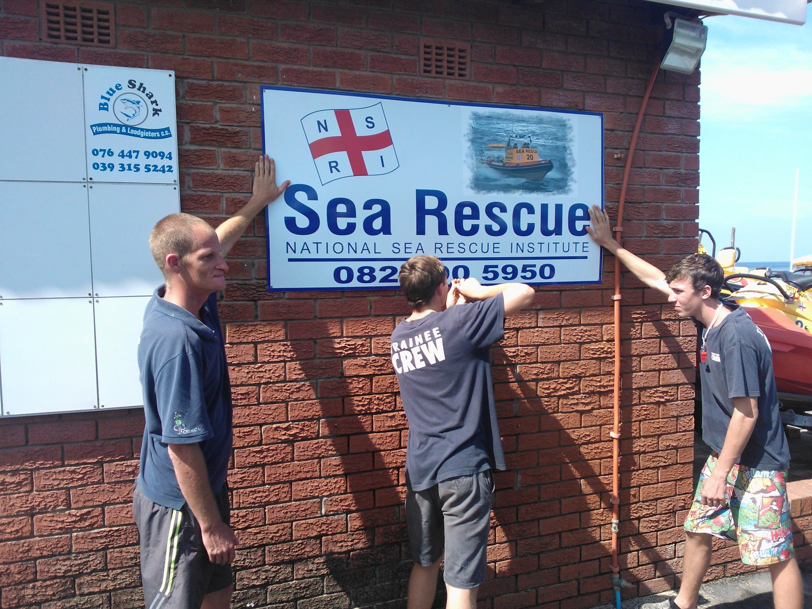 Crew member, Justin Watson (l), trainee Morne Beattie (c), and his brother, trainee Ruahn Beattie (r), fitting the signage on the town side of the base.