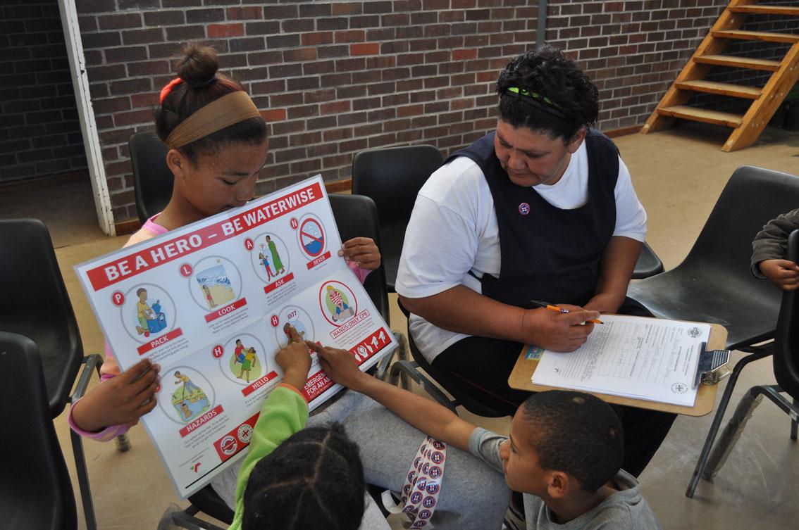 Juffrou Jeanetta Visagie voltooi die WaterWise-verslag, terwyl die kinders na hul nuwe plakaat kyk.