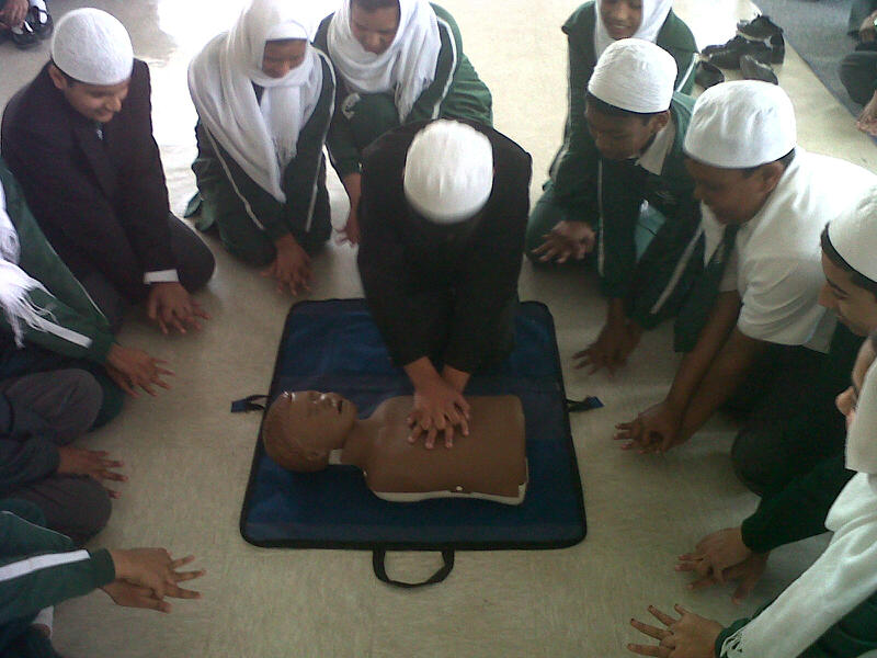 Habibia children are taken through bystander CPR.