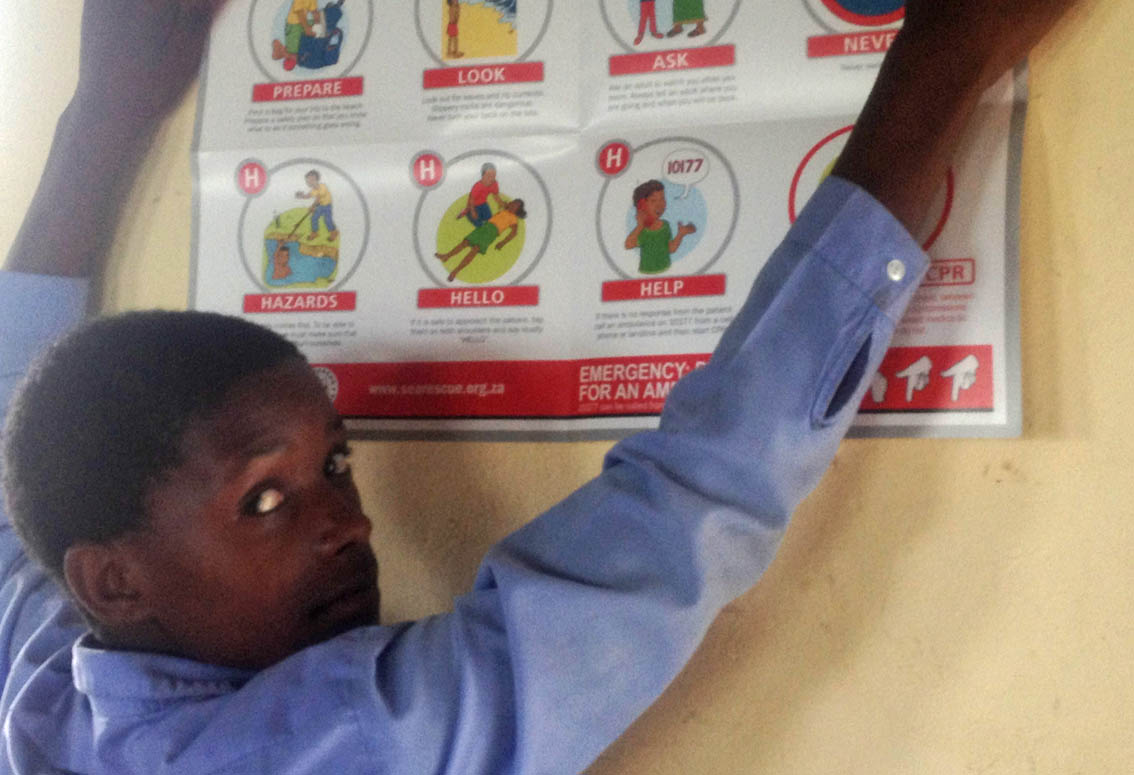 A child puts up the WaterWise poster at Ekudonseni Primary.