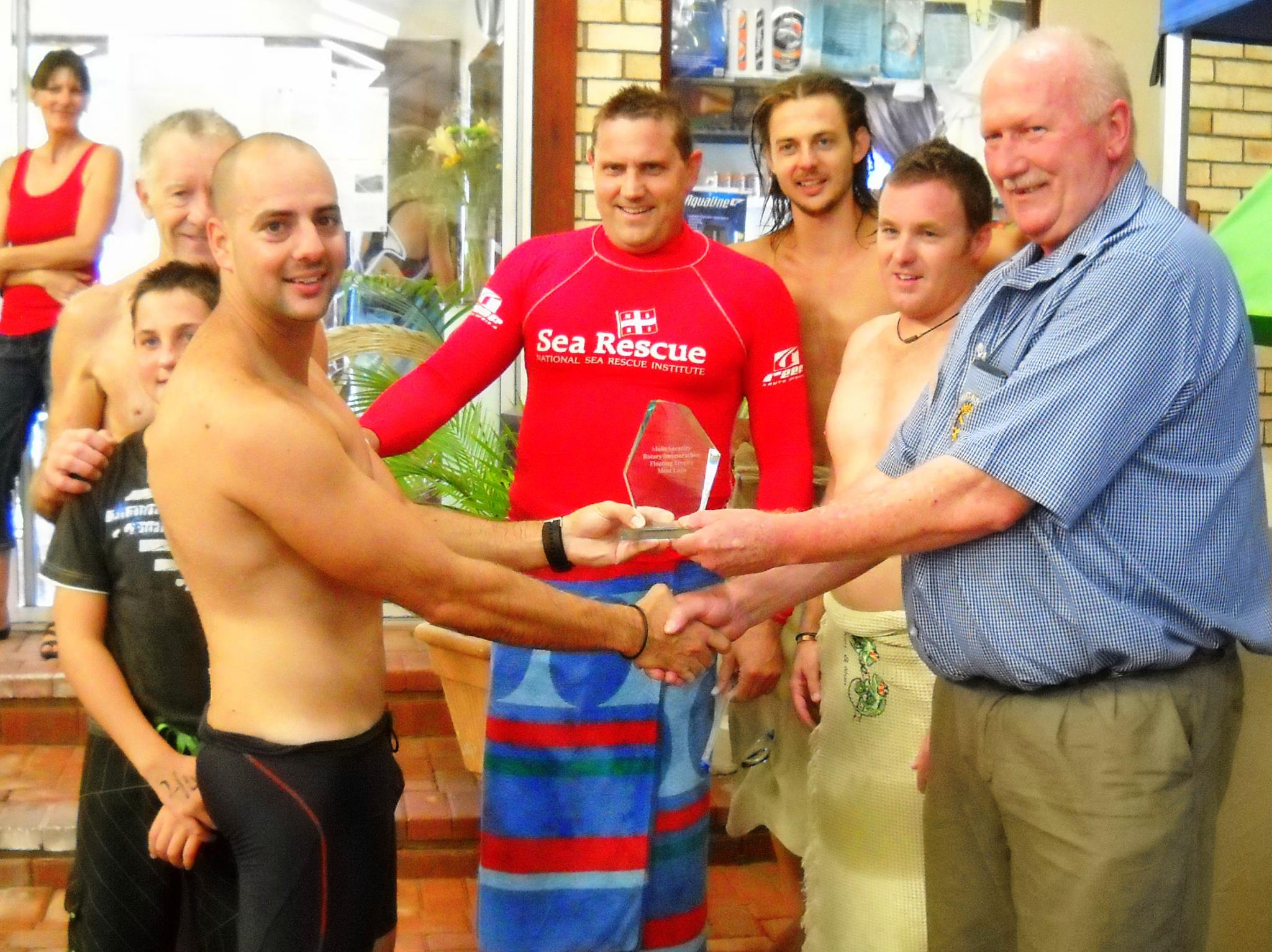 Port Alfred Station Commander Juan Pretorius receives the trophy from Colin Maclachlan, Port Alfred Rotary president.