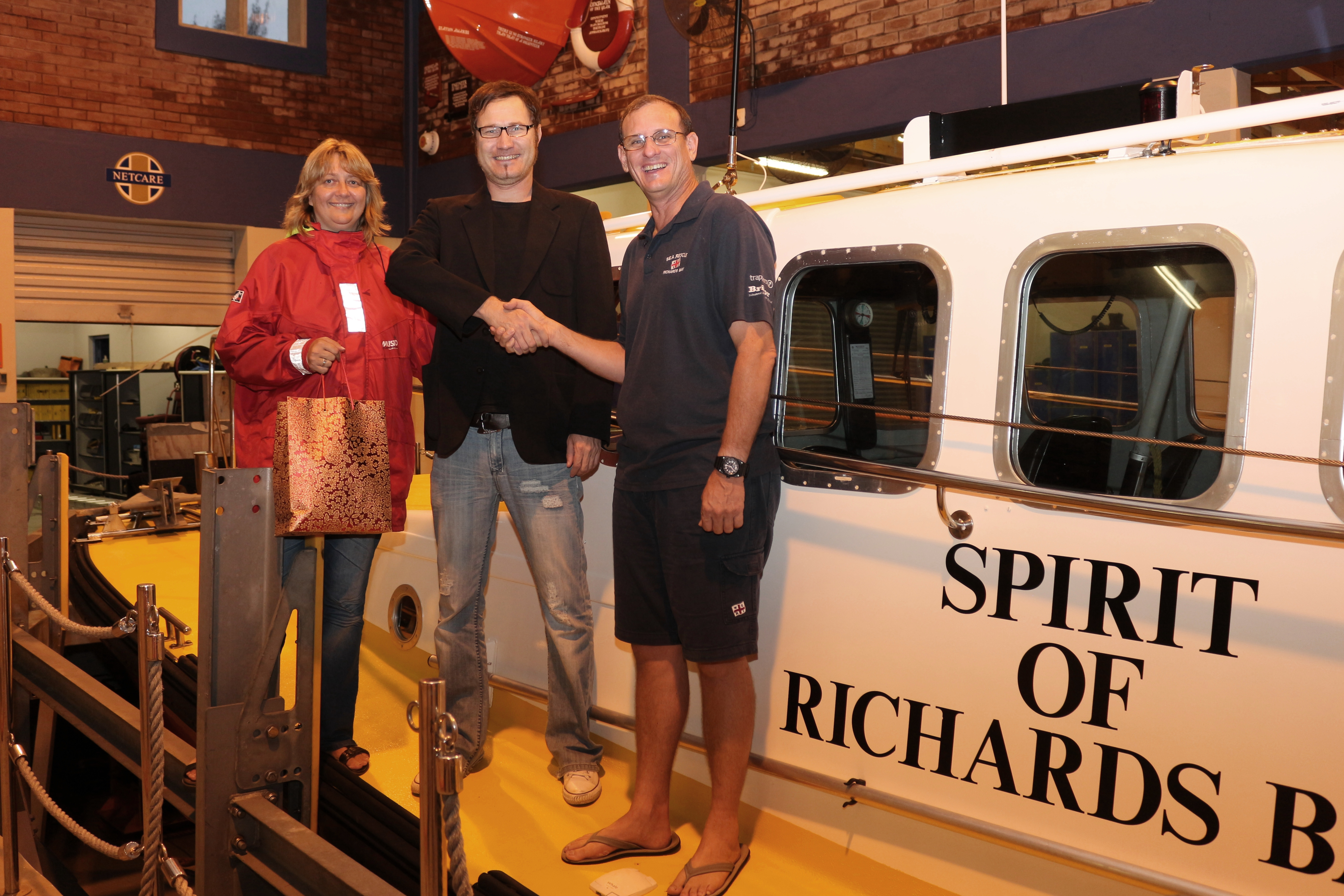 Anton De Waal (centre) receives his winner's hamper from NSRI volunteer Brynn Gericke and Richards Bay Station Commander Dorian Robertson.