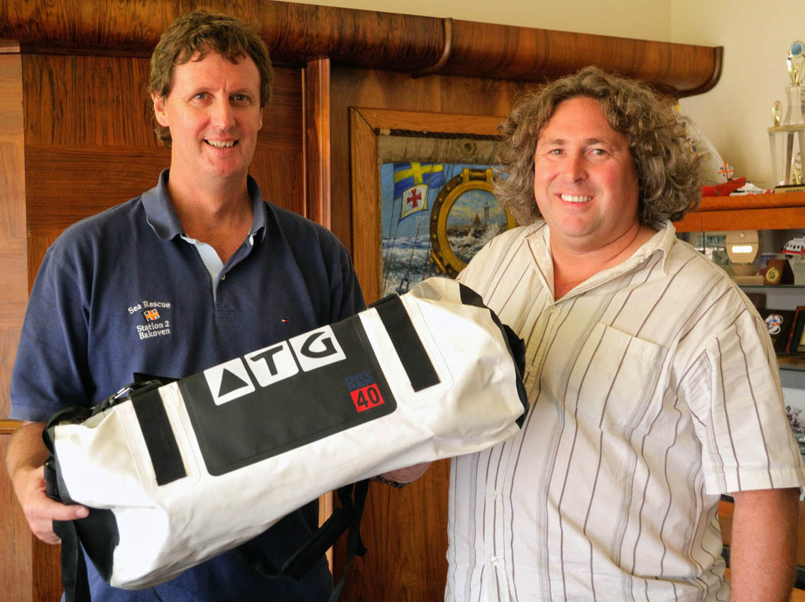 Sea Rescue's Andrew Ingram receives one of the 44 waterproof ATG bags donated by Michnus Olivier of All Terrain Gear.