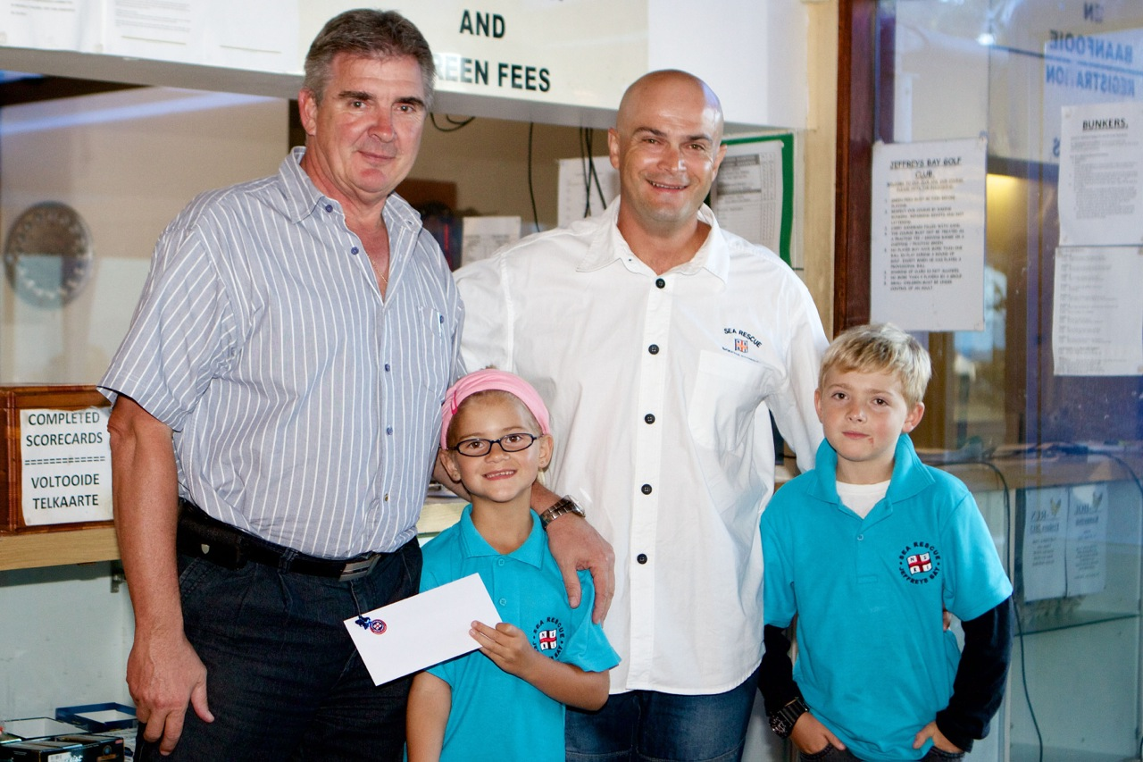 Ronnie Wansink receiving his prize from Station Commander Rieghard Janse Van Rensburg and his kids.