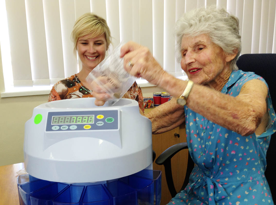 Laura Du Preez and Joan Wilkins count donations using the newly donated money counter.