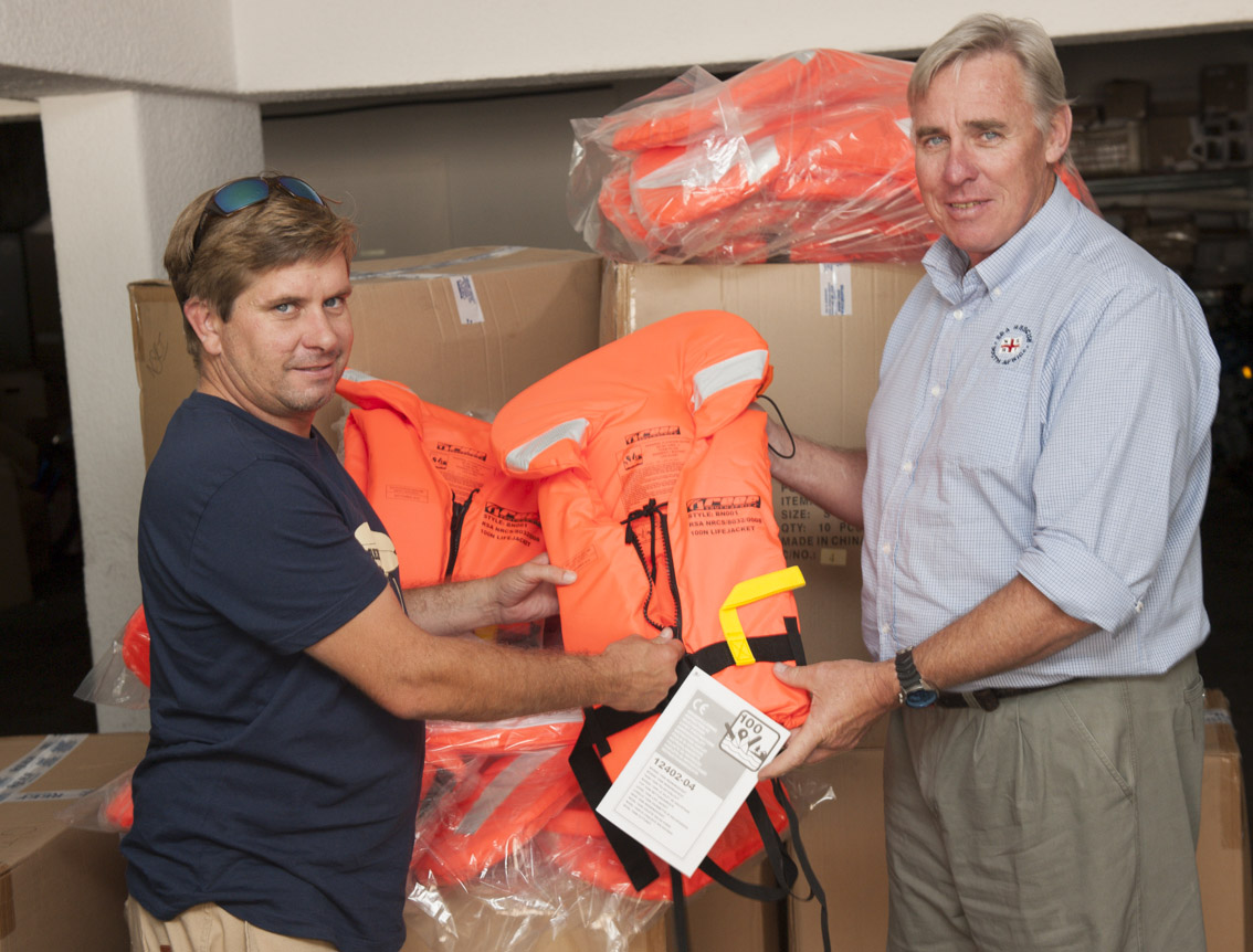 Barry Stringer presents Cleeve Robertson with the life jackets.