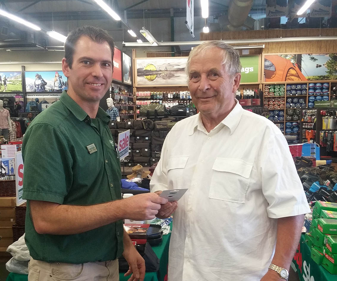 Wayne Prinsloo Tygervalley Outdoor Warehouse store manager hands Mr Kleibeler at the hand over of his voucher.